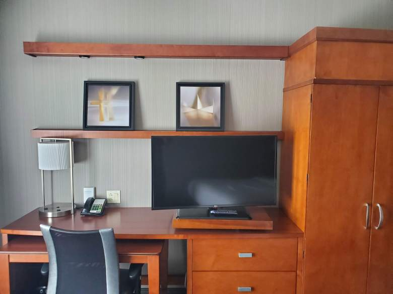Desk area with chair and tv at Courtyard by Marriott
